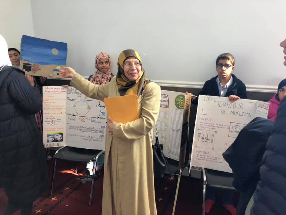 A woman points to the children's projects behind her