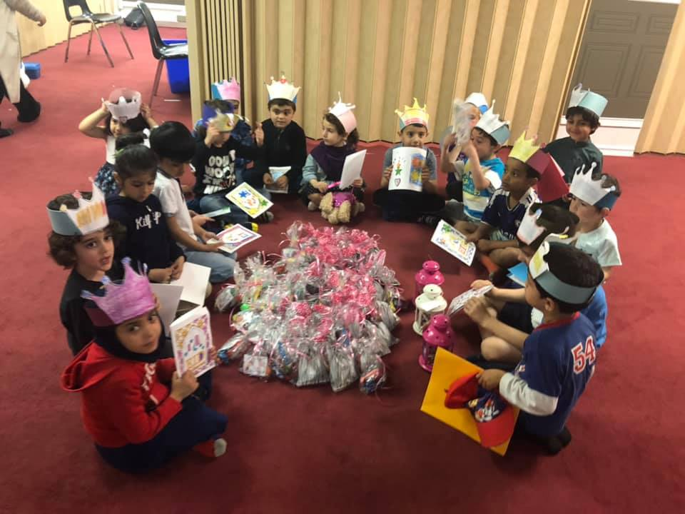 Kids sit in a circle with paper crowns on, holding booklets